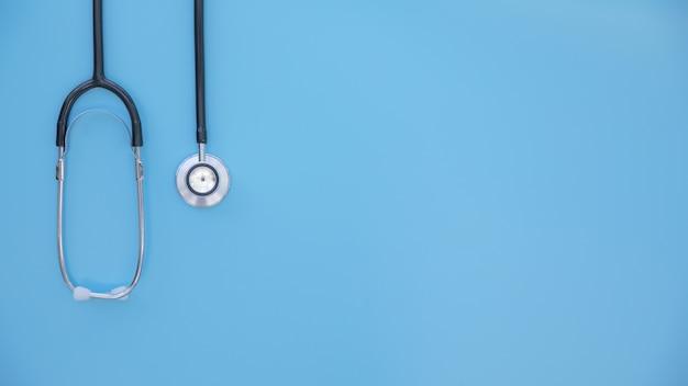 Stéthoscope noir plié, sur fond bleu clair