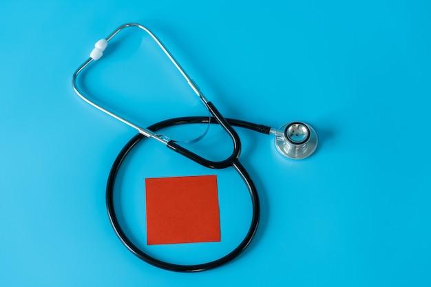 Stéthoscope et note adshive rouge sur l'espace bleu. concept médical et de soins de santé