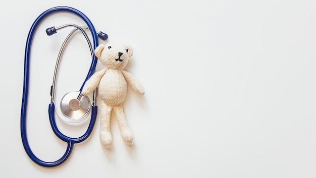 Stéthoscope et ours en peluche isoler sur fond blanc. mise au point sélective.