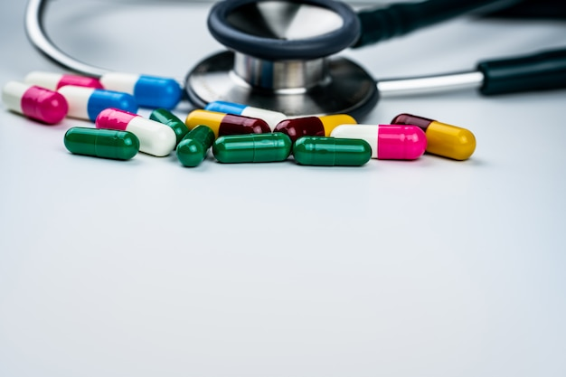 Stéthoscope avec pile de pilules antibiotiques sur fond blanc