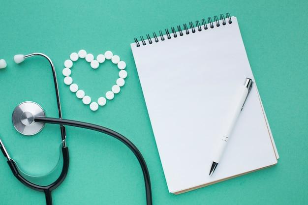 Stéthoscope et pilules avec bloc-notes