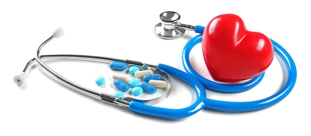 Stéthoscope, pilules et coeur, isolé sur blanc