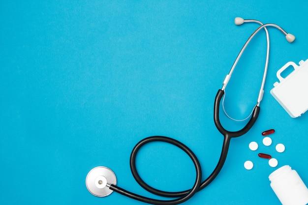 Stéthoscope avec des pilules sur fond bleu. concept de soins de santé. vue de dessus, mise à plat, espace de copie.