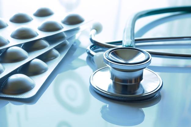 Stéthoscope et pilules avec reflet et teinte bleue