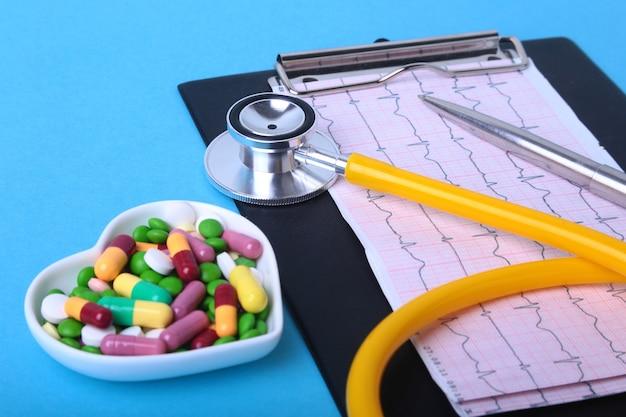 Stéthoscope, pilules rx assorties et pilules colorées sur une assiette.