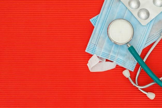 Stéthoscope et pilules sur une vue de dessus de table rouge avec espace libre
