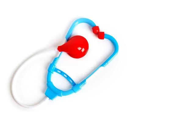 Stéthoscope en plastique jouet de couleur rouge et bleu sur fond blanc, mise à plat