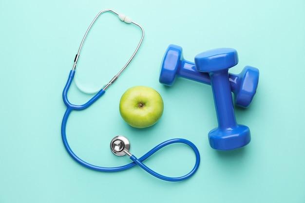 Stéthoscope, pomme et haltères sur fond de couleur