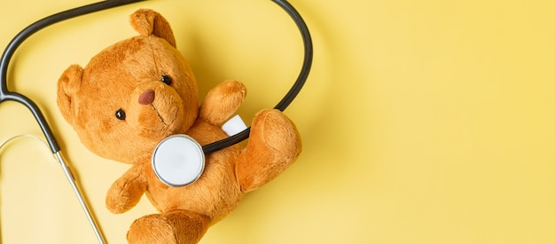 Stéthoscope avec poupée ours sur fond jaune pour soutenir la vie et la maladie des enfants. mois de sensibilisation au cancer infantile de septembre, concept de soins de santé et d'assurance-vie