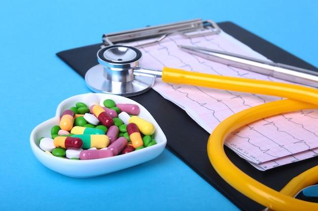 Stéthoscope, prescription et pilules assorties colorées et capsules sur plaque.