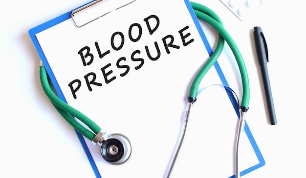 Stéthoscope et presse-papiers bleu avec texte de pression artérielle sur la feuille de calcul isolé sur blanc
