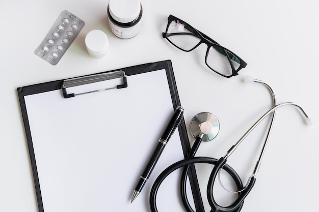 Stéthoscope avec presse-papiers et médecine, vue de dessus, espace copie, concept de soins de santé