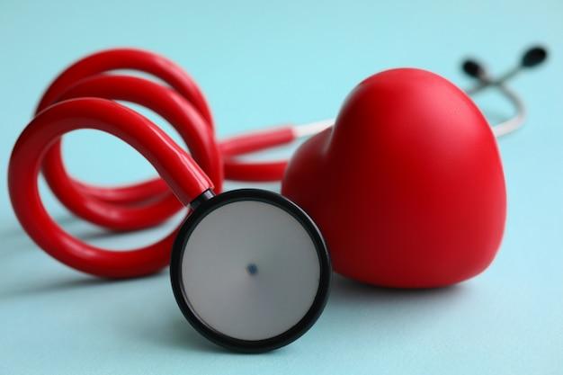 Stéthoscope rouge avec coeur sur fond moderne bleu