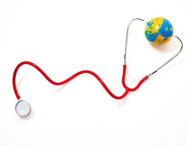 Stéthoscope rouge avec globe sur fond blanc