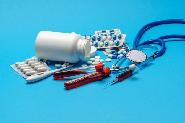 Stéthoscope, seringue, thermomètre, tube à essai sanguin et boîte de pilules sur la vue de dessus de la surface bleue avec