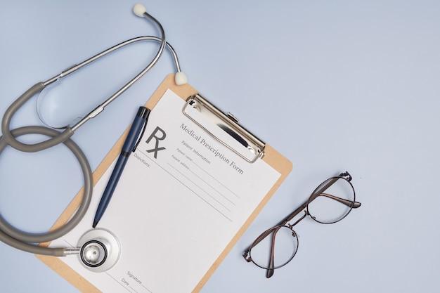 Stéthoscope, un stylo et un carnet de prescription vierge. concept de médecine ou de pharmacie. formulaire médical vide prêt à être utilisé. technologie de l'information médicale moderne.