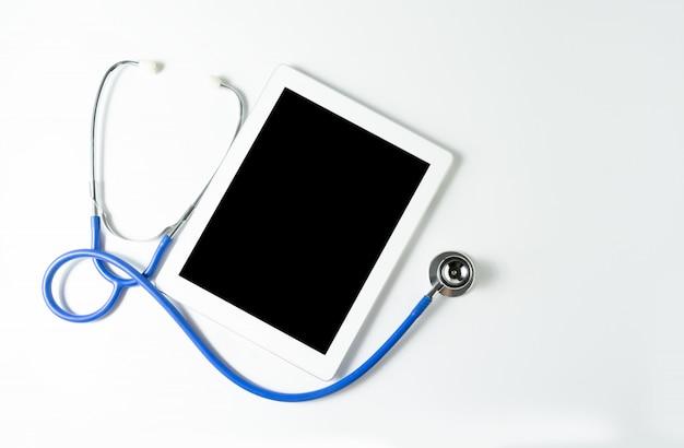 Stéthoscope et tablette sur fond blanc, espace copie pour votre texte