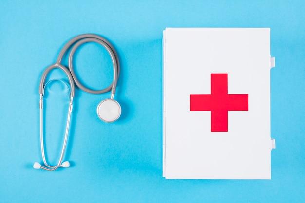Stéthoscope et trousse de premiers soins blancs sur fond bleu blanc