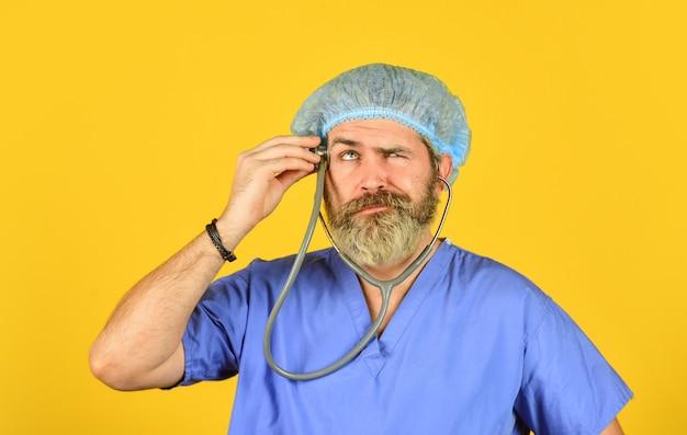 Stéthoscope uniforme de docteur barbu. check-up médical. aide médicale. prends soin de toi. burnout et maladie du système nerveux. surveiller les symptômes. assurance médicale. notion de virus. hôpital de travail de l'homme.