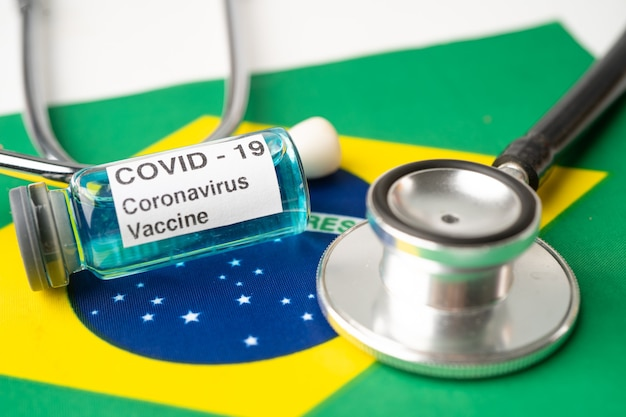 Stéthoscope avec vaccin covid-19 coronavirus sur le drapeau du brésil.