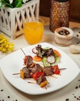 Stick barbecue avec viande, pomme de terre et tomate avec salade de légumes et jus d'orange.