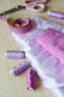 Still life fournitures de couture ciseaux fils fermeture éclair et tissu se trouvent sur une table en bois