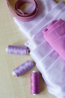 Still life fournitures de couture fils à glissière et tissu se trouvent sur une table en bois
