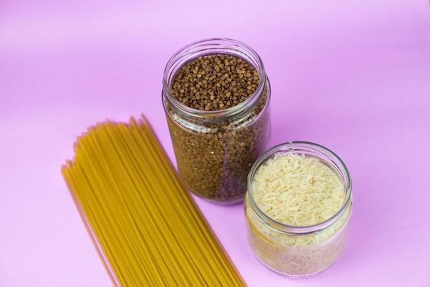 Stock de nourriture pour la période d'isolement de la quarantaine sur fond violet. riz, sarrasin, spaghetti. livraison de nourriture, don. copyspace