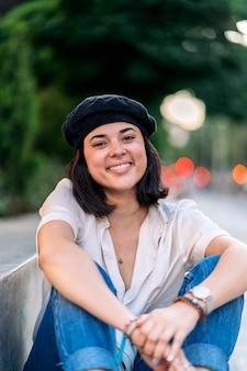 Stock photo d'une jeune femme posant et regardant la caméra. elle est assise sur un banc dans la rue. elle sourit.