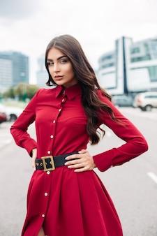Stock photo d'un magnifique mannequin confiant avec de longs cheveux bruns ondulés et maquillage posant dans la rue en élégante robe rouge vif et ceinture noire regardant la caméra