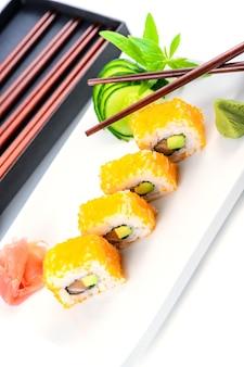 Stock photo de makis sur une assiette avec des baguettes présentées avec du gingembre et du wasabi