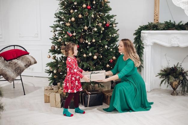 Stock photo de mère aimante en robe verte donnant sa petite fille en pyjama robe un cadeau de noël. ils sont à côté d'un arbre de noël joliment décoré sous la neige.