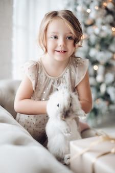 Stock photo portrait de jolie petite fille en robe de fête avec joli lapin dans ses bras assis sur le canapé. arbre de noël décoré flou en arrière-plan.