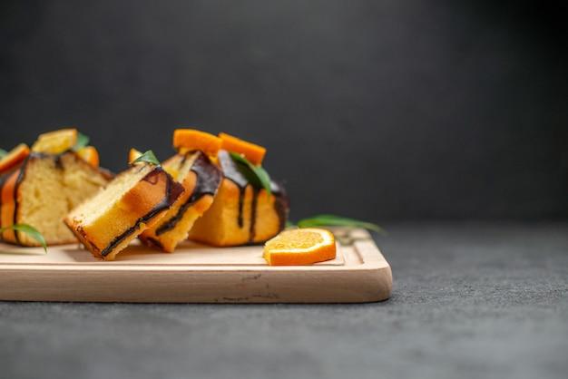 Stock photo de tranches de citron frais et de tranches de gâteau haché fraîchement cuit sur fond sombre