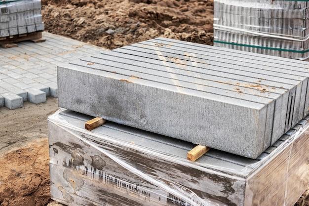 Stockage des bordures de béton sur palettes sur le chantier. préparation pour l'installation de dalles de pavage et de bordures en béton. entrepôt de produits finis.