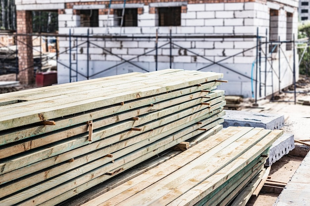 Stockage de planches et de matériaux de construction sur le chantier. préparation du matériel pour la construction d'une maison en béton cellulaire.