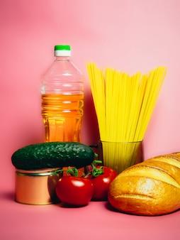 Stocks de nourriture de crise d'approvisionnement alimentaire pour la période d'isolement de quarantaine sur rose. vermicelles, pâtes, conserves, bananes, beurre, pain.