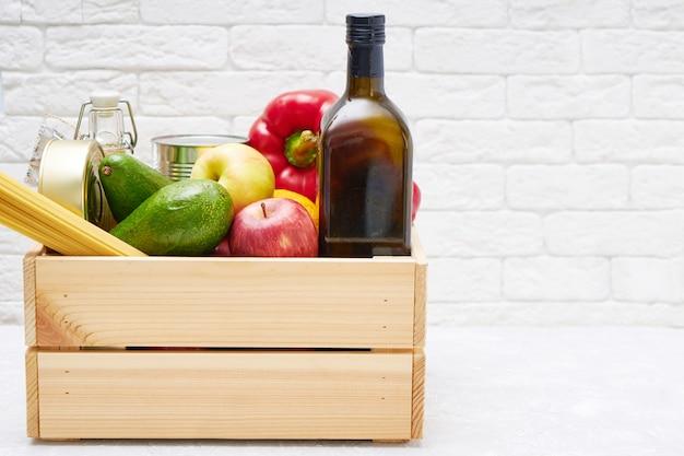 Stocks de nourriture dans une boîte en bois. légumes, huile, fruits, conserves, pâtes. don, livraison de nourriture, coronavirus