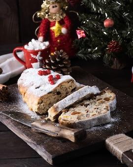 Stollen un gâteau européen traditionnel avec des noix et des fruits confits, est saupoudré de sucre glace et coupé en morceaux sur une planche de bois brun