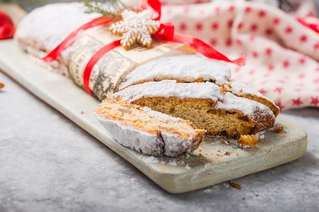 Stollen un gâteau européen traditionnel avec des noix et des fruits confits, est saupoudré de sucre glace et coupé en morceaux