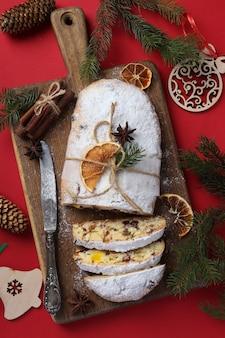 Stollen savoureux de noël avec des fruits secs, des baies et des noix sur fond rouge. friandises traditionnelles allemandes. format vertical