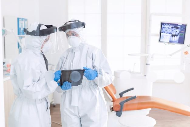 Stomatologues portant une combinaison d'epi discutant du diagnostic du patient pendant covid-19. équipe de stomatologie dans un cabinet dentaire portant une combinaison de protection contre le coronavirus contagieux pendant la pandémie mondiale.