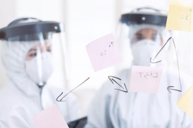 Stomatologues vêtus d'un costume ppe pendant covid-19 par mesure de sécurité. équipe médicale du bureau de stomatologie portant une combinaison dans un cabinet dentaire écrivant des idées sur des notes autocollantes.