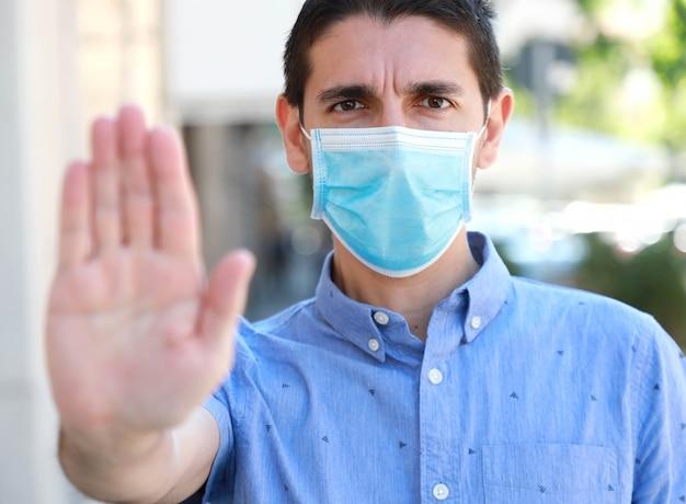 Stop covid-19 homme portant un masque chirurgical sur le visage faisant le geste stop regardant la caméra à l'extérieur.