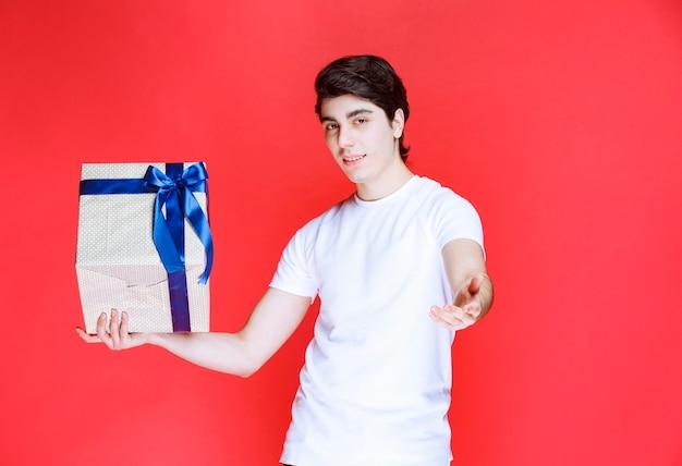 Storeman tenant une boîte cadeau blanche et demandant le paiement