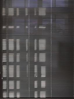 Des stores sombres ferment la fenêtre ensoleillée. fond de fenêtre sombre