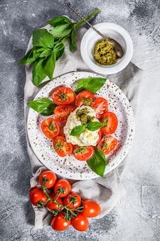 Stracciatella au fromage italien (burrata) sur une petite assiette servie avec des tomates fraîches et du basilic.