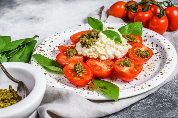 Stracciatella au fromage italien (mozzarella buffalo) sur une petite assiette servie avec des tomates fraîches et du basilic.