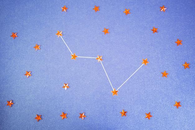 Des strass oranges en forme d'étoiles sont disposés dans la constellation de cassiopée.