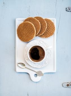 Strasswafels au caramel hollandais et tasse de café noir sur une planche de service en céramique blanche